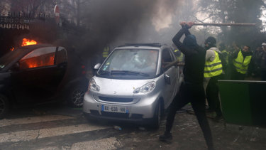 Hooded demonstrators smash a car during a demonstration in Paris on Saturday.