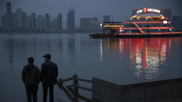 Residents chat along the Yangtze River in Wuhan in central China's Hubei province on Sunday. Quarantine in the the epicentre of China's coronavirus outbreak is to be formally lifted on Wednesday.