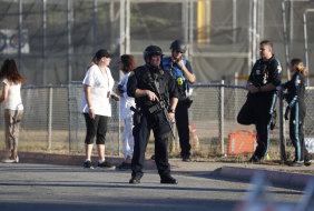 A police officer stands guard at Gilroy High School after a deadly shooting at the Gilroy Garlic Festival.