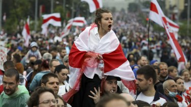 A woman covers herself by an old Belarusian national flag reacts as opposition supporters gather in front of police line toward the Independence Palace, residence of the President Alexander Lukashenko in Minsk, Belarus.