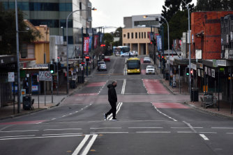 A lone person walks across Moore Street, Liverpool on Saturday as Sydney bunkers down under tightened restrictions announced by Premier Berejiklian on Friday.