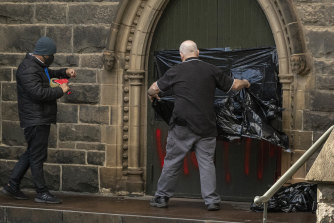 Workers cover graffiti at St Patricks Cathedral on Wednesday morning.