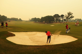 Sergio Garcia plays out of a bunker under a thick layer of haze over the Australian Golf Club in Sydney on Thursday.