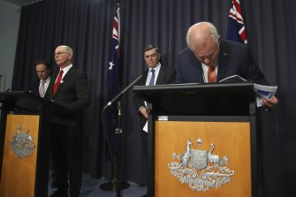 (From left) Greg Hunt, Professor Paul Kelly and Professor Brendan Murphy with Prime Minister Scott Morrison, who is taking a closer look at his notes during a press conference on Thursday night.