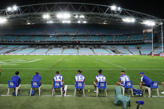 Bulldogs interchange players and support staff, seated well apart, look on at an empty ANZ Stadium.