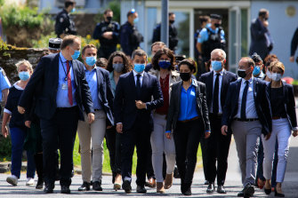 French Interior Minister Gerald Darmanin, centre, arrives at the police station where the officer was stabbed.