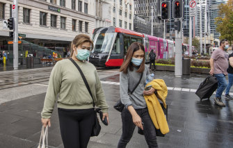 People wearing face masks in Sydney's CBD, after the NSW government introduced new restrictions on Thursday.
