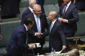 Treasurer Josh Frydenberg is congratulated by Prime Minister Scott Morrison and colleagues after delivering the budget speech.
