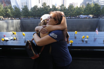Melinda Moran and Haydee Lillo embrace after finding out they lost people who knew each other, next to the North Reflecting Pool during a ceremony at the National September 11 Memorial & Museum in New York.
