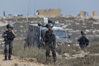 Israeli border police secure a road leading to a newly established Israeli settlers outpost, seen in the background, during clashes with Palestinian protesters in the West Bank village of Tormusayya, last month.