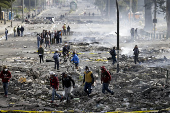 Pedestrians walk among the debris of barricades set by anti-government protesters in Quito on Sunday.