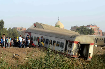People gather at the site where a passenger train derailed injuring at least 100 people, near Banha, Qalyubia province, Egypt, Sunday, April 18, 2021.