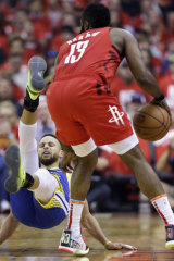 Golden State star Stephen Curry, left, hits the boards after a bump from Rockets guard James Harden.