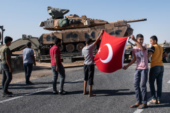 People hold a Turkish flag as they give their support to the Turkish military during the deployment of tanks to Syria on October 12, in Akcakale, Turkey.