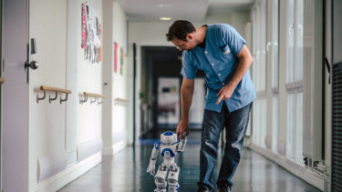 Mickael Feret, a nurse, walks with a robot named Zora at Jouarre, a nursing facility an hour outside Paris.