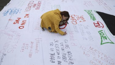 A woman writes a message on a protest poster during an anti-government demonstration in Bogota.