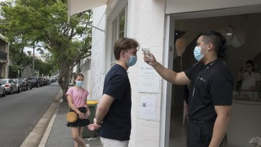 Shoppers have their temperature taken before entering a jewellery store in Paddington.
