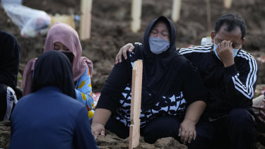 Family members weep during the burial of a relative at Jakarta's Rorotan Cemetery which is reserved for those who die of COVID-19.