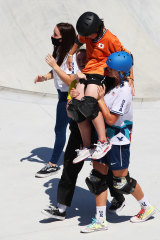 Japan's Misugu Okamoto is chaired off, by Australia's Poppy Starr Olsen and American Bryce Wettstein.