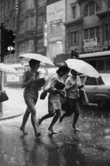 Three women run for cover on the corner of Swanston Street and Flinders Lane.
