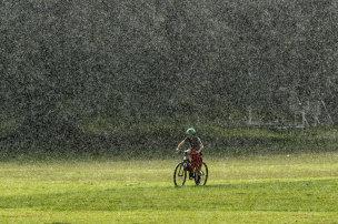 A cyclist rides through heavy rain at Queens Park in mid-2020.