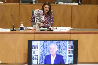 Commitee chair Senator Sarah Hanson-Young holds up a front page of the Daily Telegraph as she puts a question to former Prime Minister Malcolm Turnbull as he appears via videoconference during a hearing on media diversity in Australia at Parliament House in Canberra.