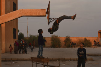 A child shows off his gymnastics skills at a high school full of people fleeing the fighting at the Syria-Turkey border.