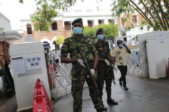 Sri Lankan government soldiers stand guard at the entrance to a ballot counting centre in Colombo on Thursday.