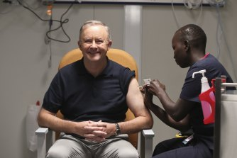 Opposition Leader Anthony Albanese receives a COVID-19 vaccination from registered nurse Yom Mapiou.