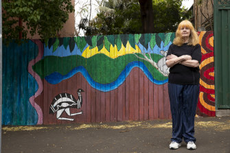 Darlington local Winsome Evans stands next to a mural painted by Darlington Primary School students