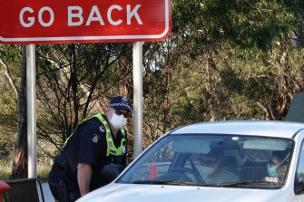 Victoria Police members stop motorists leaving metropolitan Melbourne at a checkpoint set up on the Calder Freeway between Sunbury and Gisborne earlier this month.