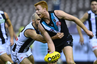 Willem Drew handballs while being tackled by Steele Sidebottom.