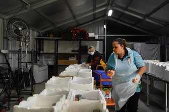 Staff at Tharawal Aboriginal Corporation in Airds prepare food care packages that will be delivered to elders.
