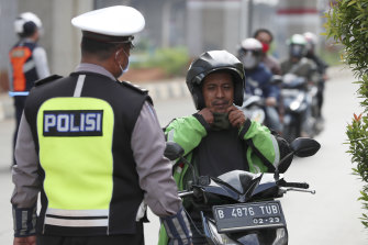 A police officer asks a man on a scooter to wear a face mask during the imposition of large-scale social restrictions in Jakarta, Indonesia.