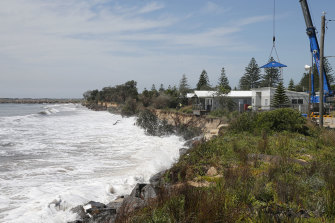 Newcastle City Council use a crane to move cabins from the council owned Stockton Caravan Park as erosion from large swell threatens to undermine them into the sea.