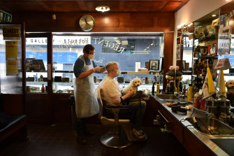 Barber Alan Kelly tends to customer Anthony Remedy at the Regents Barbers shop in Dublin, Ireland.