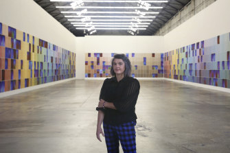 Artist Kate Mitchell stands in front of her installation, which she's still completing as she hunts down photographic subjects with obscure occupations.