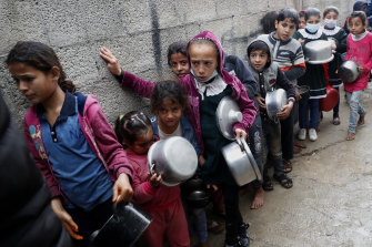 Palestinian children wait in line while holding pots to receive free meals of green pea stew cooked by Samera Abu Amra, unseen,  for distribution to poor residents in Gaza City on Thursday.