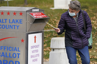 A woman inserts her ballot at a drop box in Salt Lake City.