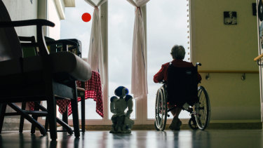 Zora squats beside a patient at Jouarre. The facility has seen some patients open up to the robot.