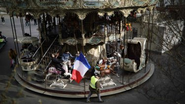 A man carrying a French national flag walks past a carousel near Sacre Coeur in Paris, on Saturday.