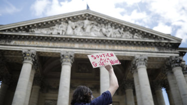 "A man holds a placards reading ""Support the black vest"" outside the Pantheon monument on Friday."