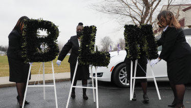 """Church staff arrange flowers that speak out """"BLM"""" before the casket of Andre Hill is brought to a hearse following his funeral in Columbos, Ohio. The 47-year-old black man, was shot and killed by a police officer in December."""