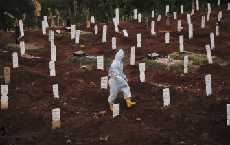 A municipal cemetery worker walks through a special cemetery for suspected Covid-19 victims in Jakarta, Indonesia, in September.