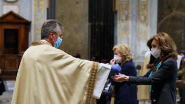 The parish priest Marco Gnavi of Santa Maria in Trastevere administers the sacrament of Communion while celebrating Mass in Rome.