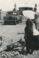 Locals watch as troops and vehicles of the 1st Battalion land on the beach at Vung Tau, Vietnam on June 8, 1965.
