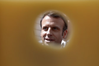 French President Emmanuel Macron is pictured through a piece of cheese as he attends the annual May Day ceremony during which French food products are displayed at the Elysee Palace, in Paris, last year.