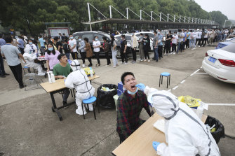 Workers line up for a coronavirus test at a large factory in Wuhan, China.