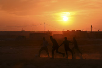 A group of men play football in the yard of a school that has become an unofficial camp for hundreds of Kurds.