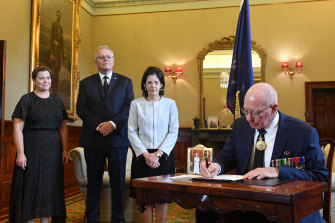 Governor-General David Hurley signs a condolence book as his wife Linda Hurley, Prime Minister Scott Morrison and his wife Jenny Morrison (left) watch on.